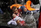 A Syrian refugee holds onto his children as he struggles to walk off a dinghy on the Greek island of Lesbos, after crossing a part of the Aegean Sea from Turkey to Lesbos September 24, 2015. REUTERS/Yannis Behrakis/File photo